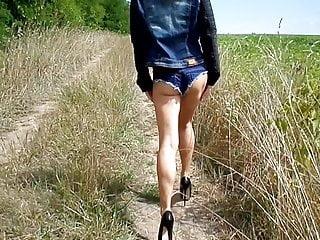 Denim fetish Denim shorts and high heels walking on a field road