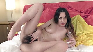 Hairy Aragne oils down her body in bed and masturbates