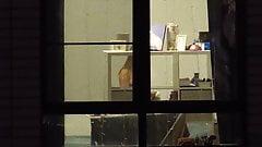 Fenster-Voyeur-Mädchen mit blanken Titten