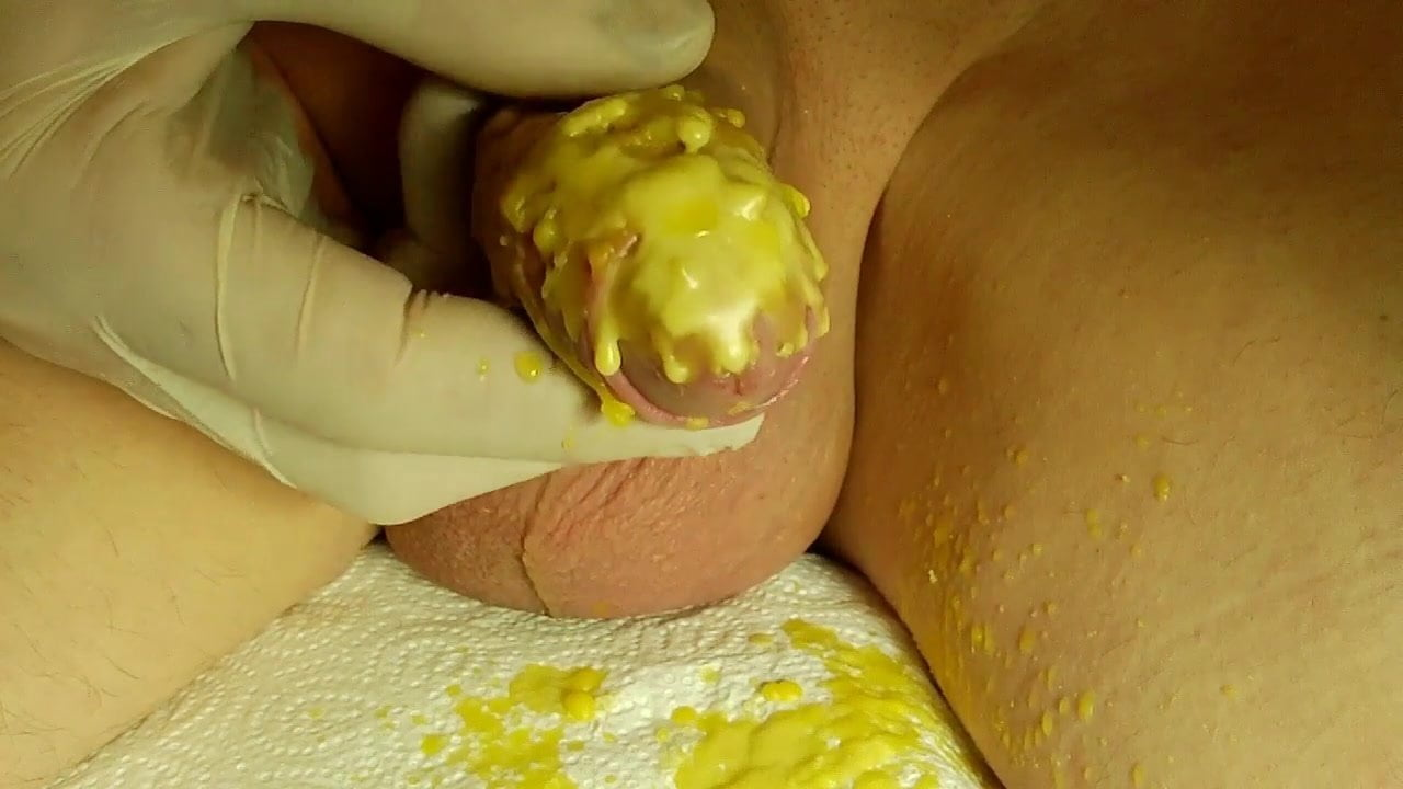 Salon master works around a hard penis in order to wax a bush