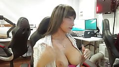 Latina sitting in office pulls out big tits and licks nipple