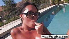 Asa Akira se couche au bord de la piscine et se fait huiler
