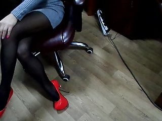 Vintage high back chair Nylon tights and heels in the office in a leather chair