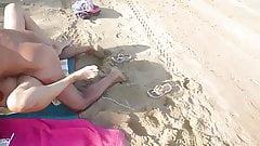 Un vieux ridé baise une jeune femme sur la plage