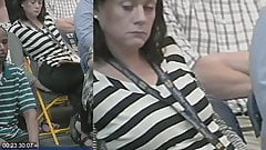 woman syntribates and smells her fingers in public meeting