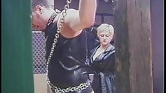 Two dominatrixes inflict pleasurable pain on restrained male slave in a dungeon