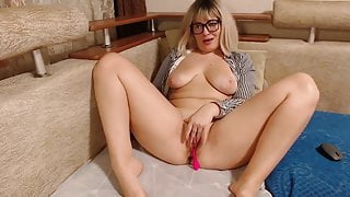 Sexy blonde in glasses caresses her horny pussy