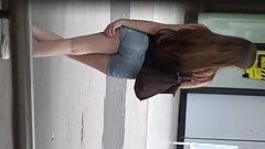 Junge Schuelerin zeigt ihre Beine und ihren sexy Hotpants-Po