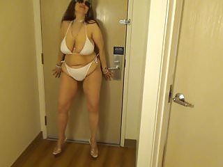 Full coverage string bikini Tinja stretches a white string bikini in 6 inch stilettos