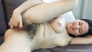 Beautiful hairy Bellavitana strips and masturbates on couch
