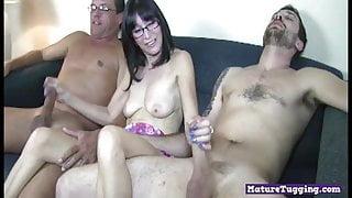 Slutty milf jerking two cocks in threesome