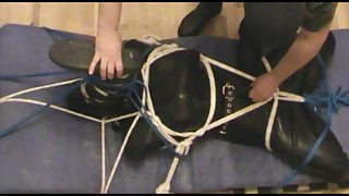 Boot on the face - Restrained rubberslave in the hogsack