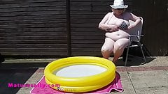 Mature with massive tits in the smallest bikini by the pool