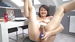 Mature shoving a dildo in her hairy pussy