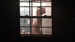 Voyeur watches sexy neighbor through window