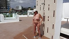 Mature woman takes a shower on the rooftop