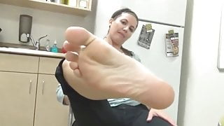 Woman shows her beautiful feet in the kitchen