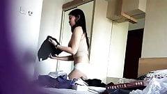 Cámara espía. sexy chica asiática cambiándose en el dormitorio