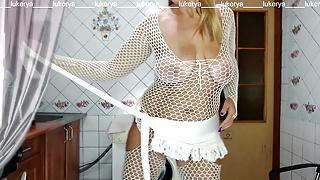 Lukerya in a white net drinks coffee on the washing machine.