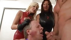 Mistresses take slave out of cage to make him suck cock
