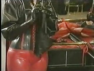 Rubber dildo pants Latex dildo pants being put on bondage girl