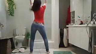 Une allumeuse brunette bandante en jeans danse