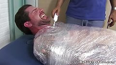 Jock Clint wrapped up to have his feet tickled BDSM style