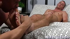 Hunk jerks his dick off while another man licks his feet