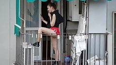 Nice teen enjoying the call on the balcony