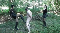 2 mistresses punishing slave in the woods