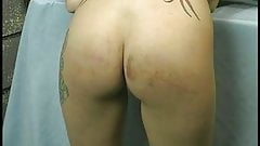 Long haired slut with tramp stamp lays across table