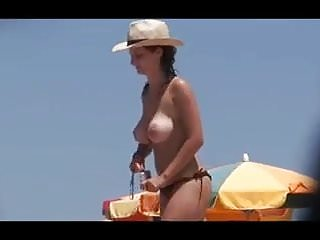 Topless girls boobs Topless girl with big boobs and a hat on the beach