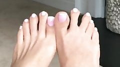 Feet play with toenails with white nail polish