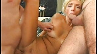 Blonde mature slut with a shaved pussy sucks cock while getting doggy fucked