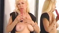 Mature and busty blonde woman pokes her pussy with a dildo