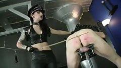 Домина сдерживает задницу голого мужчины-раба и трость тростью