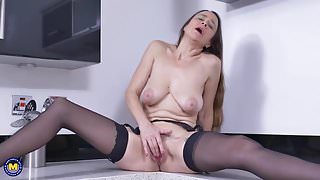 Slim mature mommy feeding pussy on kitchen