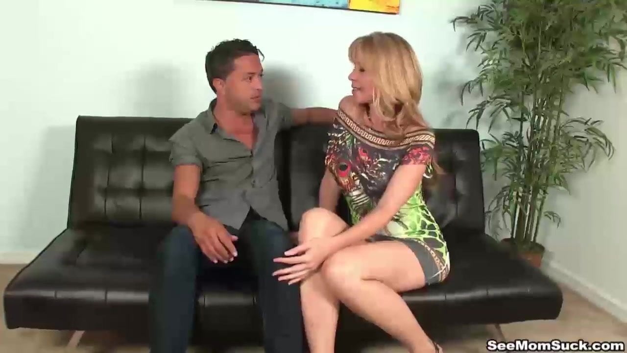 A very sexy milf with huge-sized tits is giving a young man an amazing blowjob