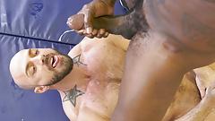 White guy growls beneath a huge cocked black bull