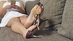 Dangling, shoeplay with sweet high-heel sandals, on couch.