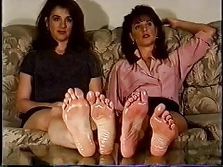 Vintage oil sunset on ocean Retro girls showing off their oiled feet.