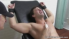 Muscly stud restrained for erotic torment and foot tickling