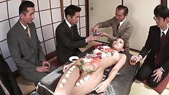 Business men eat sushi out of a naked girl's body