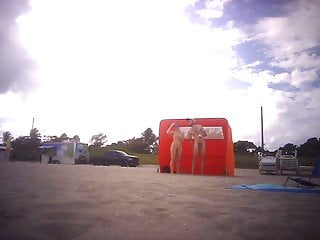 Rate nude couple - Nude couple putting on sunscreen on nude beach