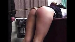 Disciplining teacher Miss Parker with hand and cane