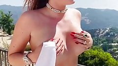 Bella Thorne taking on a balcony taking her top off